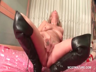 mature in leather galoshes doing herself into bed