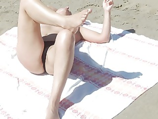 candid seaside lady sunbathing